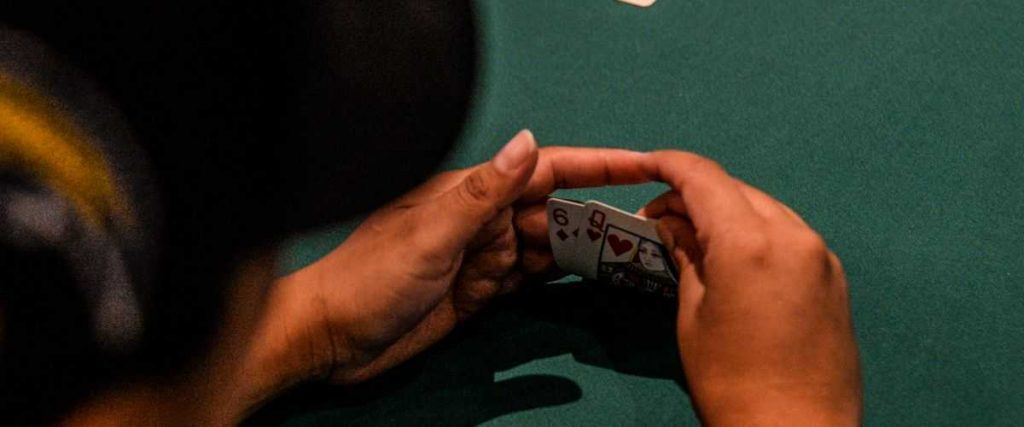 A poker player holding his cards.