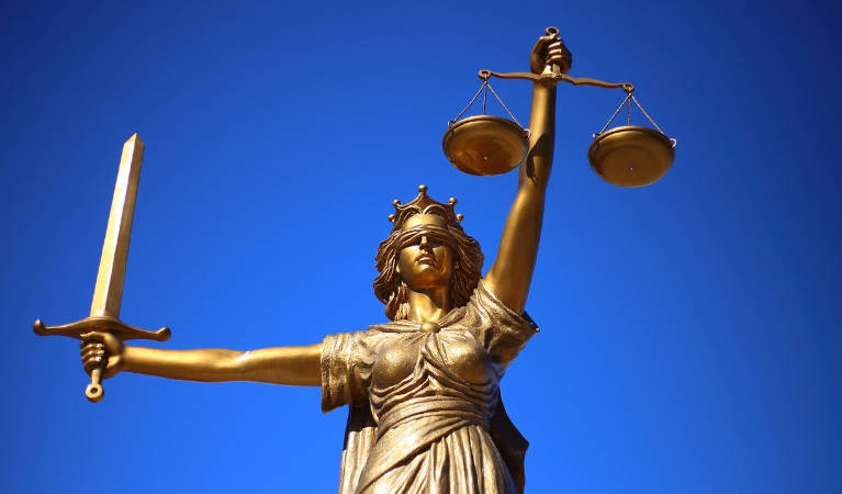 Lady Justice holding the scales blindfolded.