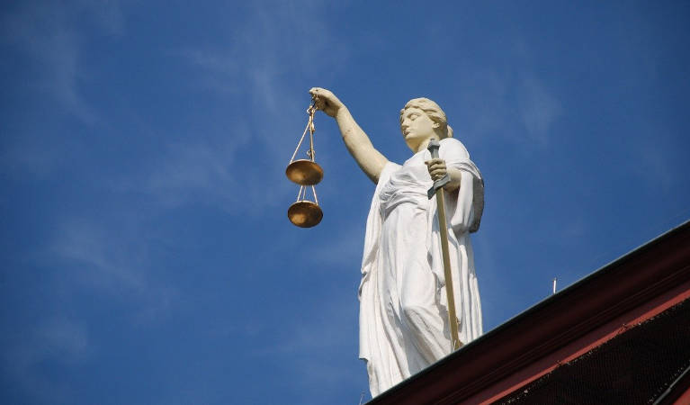 Lady Justice holding the scales on top of a court house