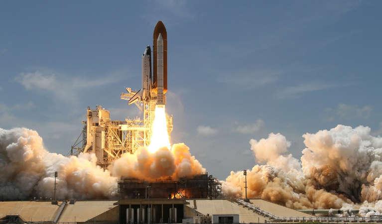 A rocket launching off a rocket pad.