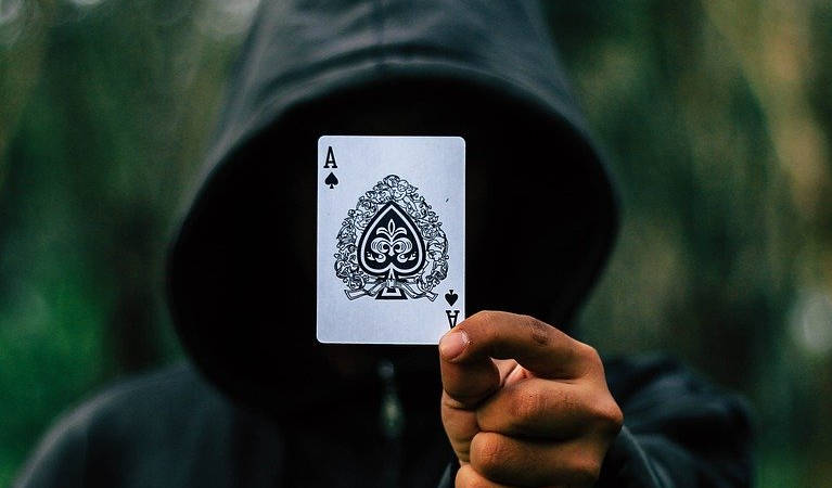 A hooded poker player holding an ace, likely demonstrating his ability to cheat.