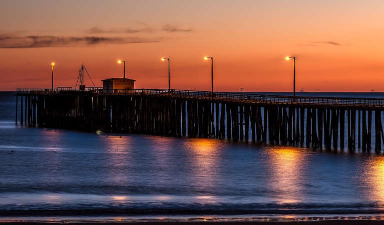 Sunset in California, with the wharf poorly lit in the dusk.