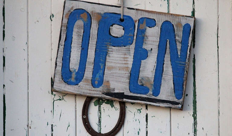 A sign saying open on a wooden door.