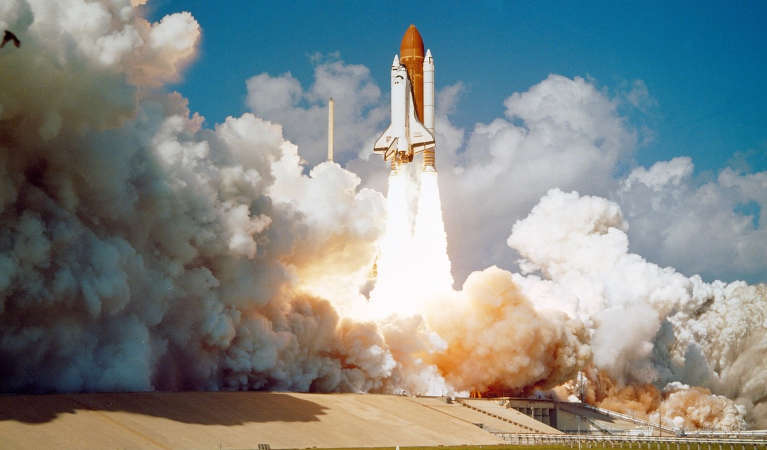 The Challenger space shuttle launching off its pad.