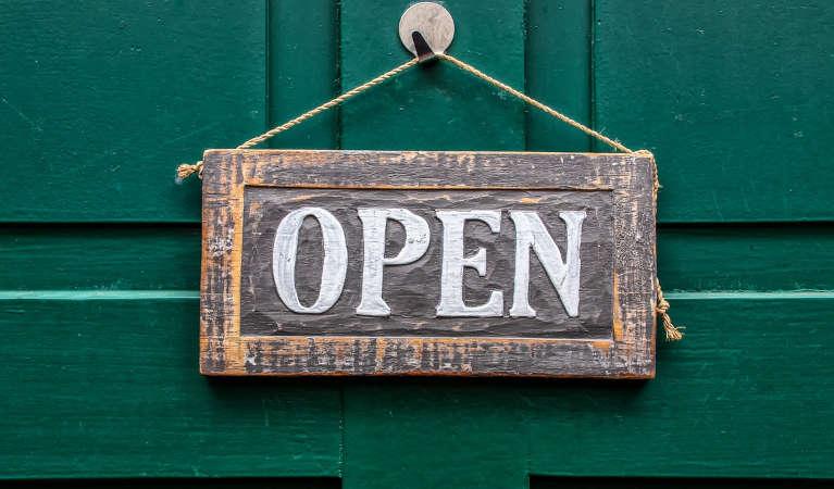 an-open-sign-against-a-green-door-background