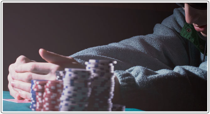 Image of UTG poker player checking his cards